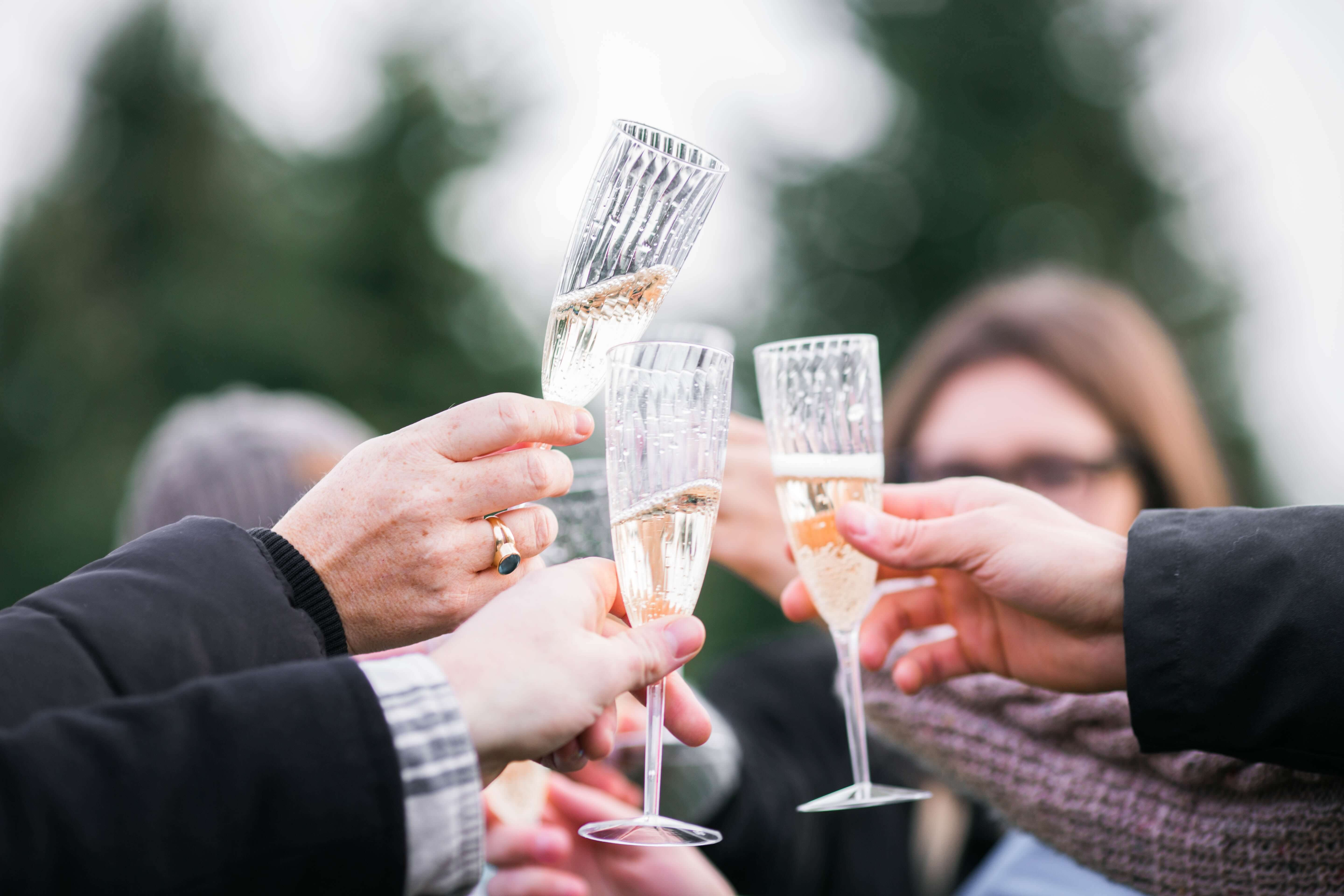 people clinking together cava glasses in the spanish wine region in catalonia